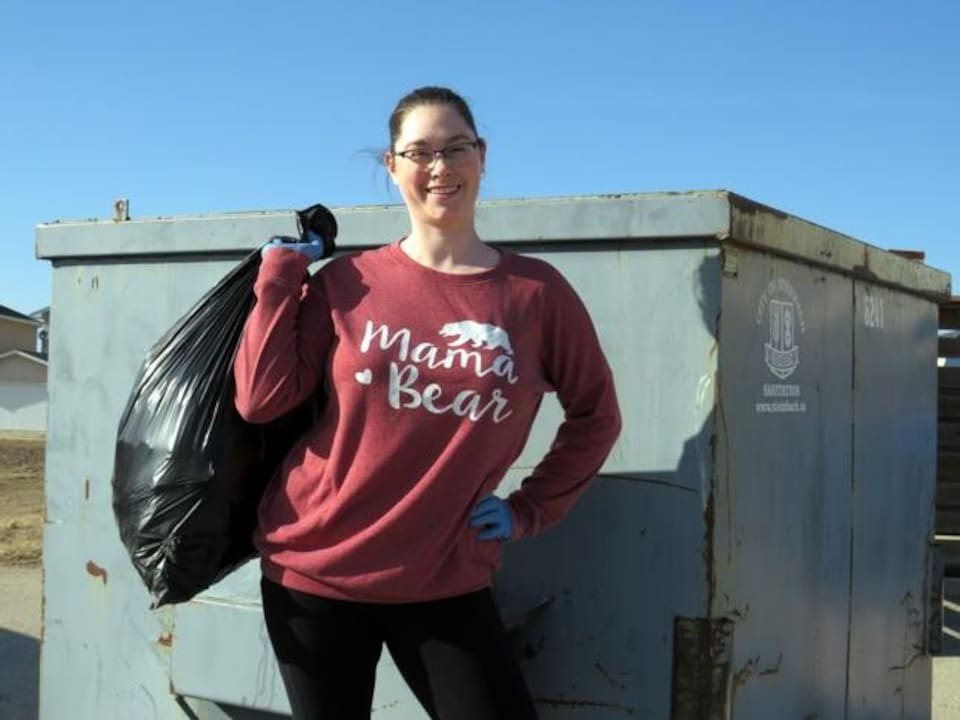 Kristen Désorcy devant une poubelle porte un sac d'ordures.