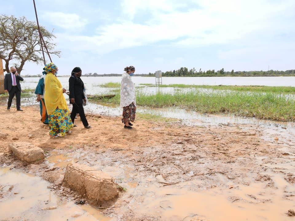 Amina J. Mohammed debout sur un terrain boueux.