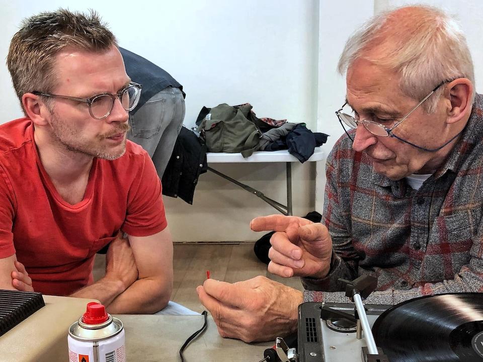 Bas Wind et un bénévole qui tente de réparer son tourne-disque.