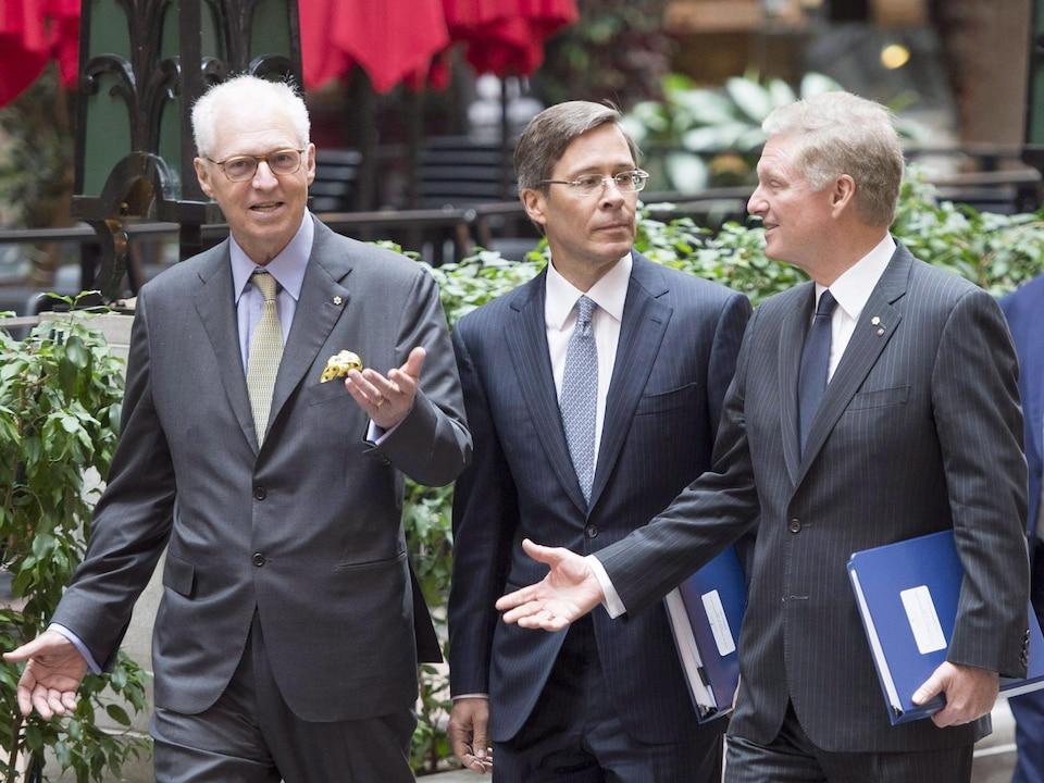 Les trois hommes marchent en discutant.