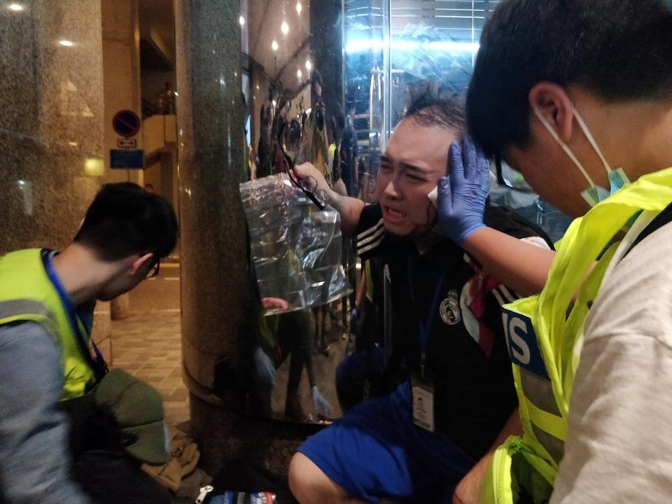 Andrew Chiu est blessé, quelqu'un lui tient l'oreille gauche avec un pansement, tandis qu'il saigne abondamment.