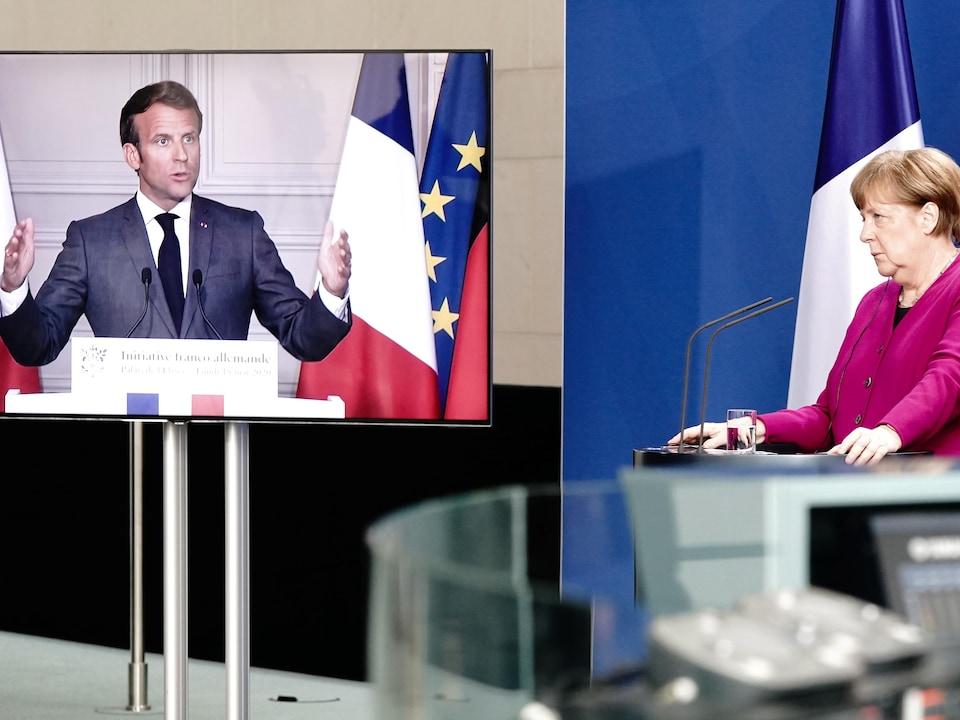 Angela Merkel est devant un lutrin et Emmanuel Macron sur un écran.