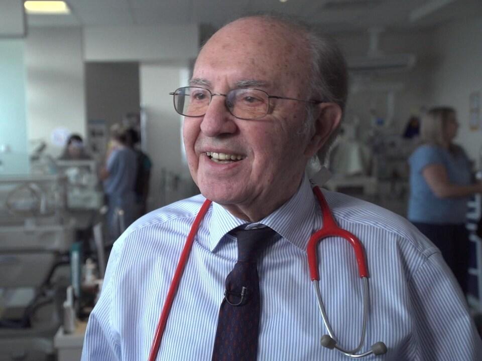 Un homme souriant au crâne dégarni et grisonnant, un stéthoscope autour du cou.