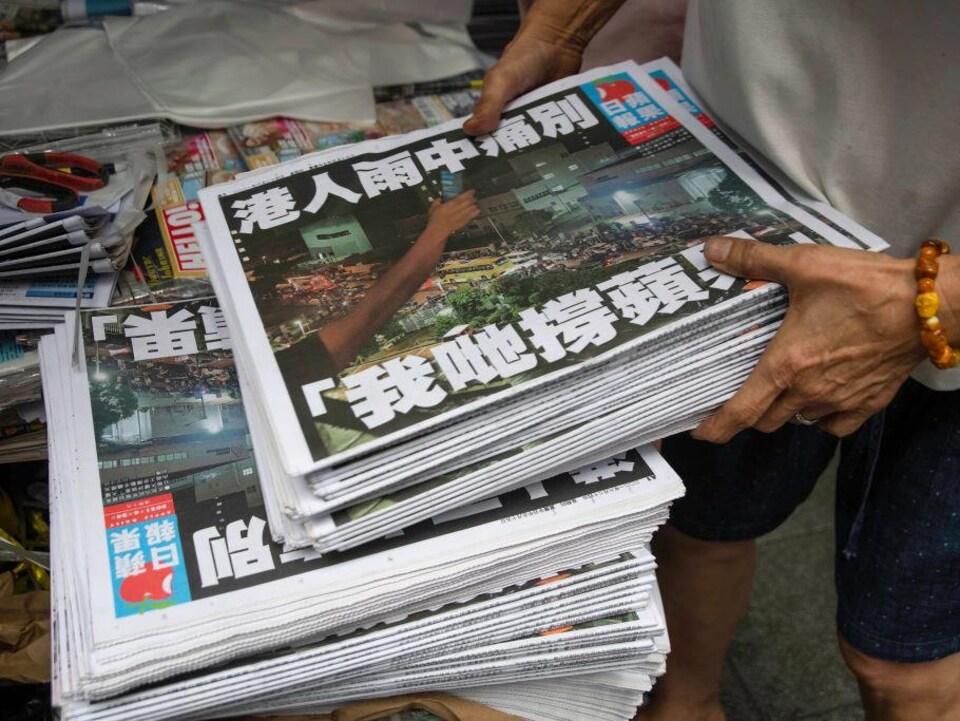 Une personne tient dans ses mains une pile de journaux.