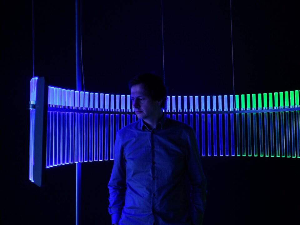 Philippe Rahm pose devant une source de lumière mauve et verte.