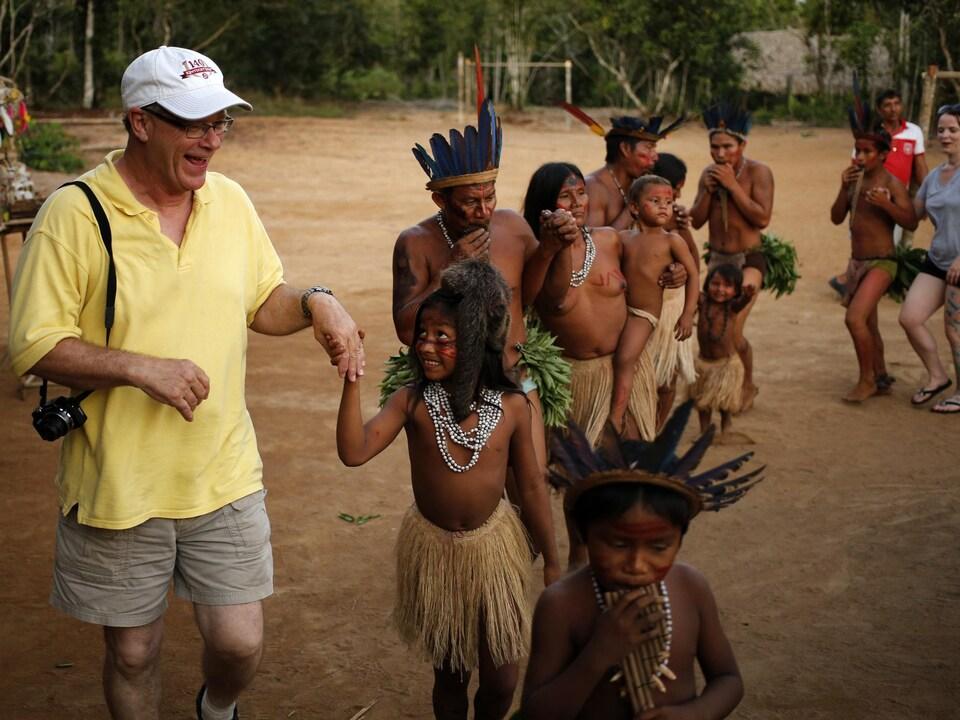 Un touriste blanc avec une casquette danse avec des jeunes à la peau foncée et une coiffe de plumes sur la tête.