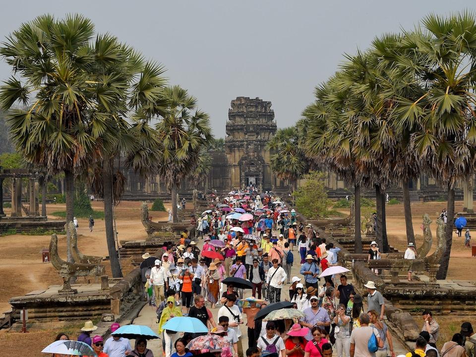 De nombreux touristes marchent dans une allée du temple d'Angkor Vat, au Cambodge.