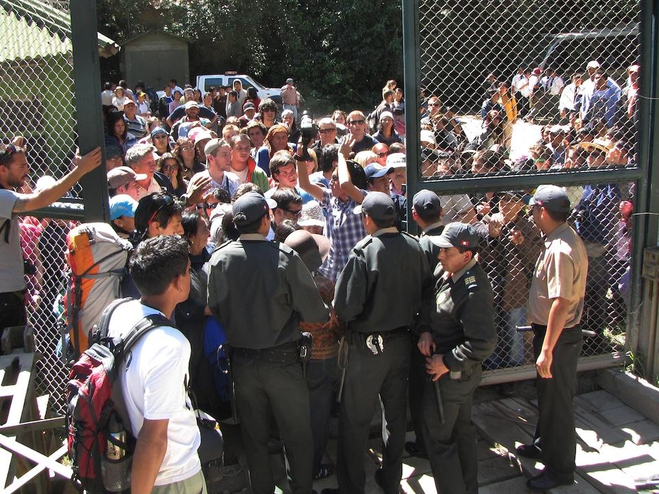 Des dizaines de touristes sont rassemblés devant une barrière, face à des gardes de sécurité qui ne les laissent pas entrer.