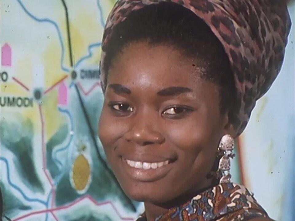 Hôtesse du pavillon de la Côte d'Ivoire souriant à la caméra