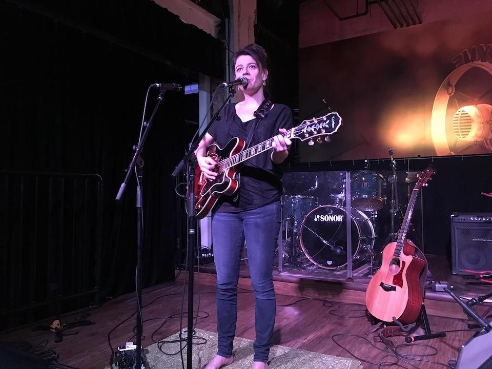 Ariane est debout sur une scène, elle chante et joue de la guitare.