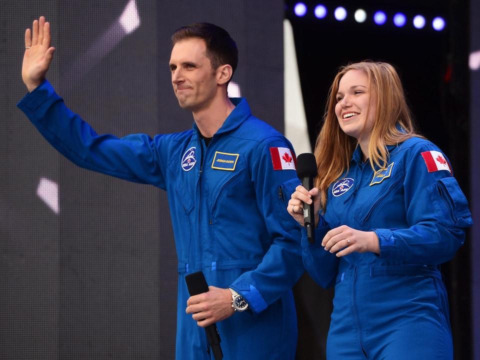 Joshua Kutryk et Jenni Sidey, vêtus de la combinaison bleue de l'Agence spatiale canadienne, saluent la foule.
