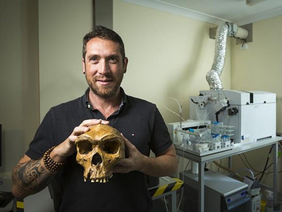 Renaud Joannes-Boyau tient dans ses mains le crâne d'un australopithèque.