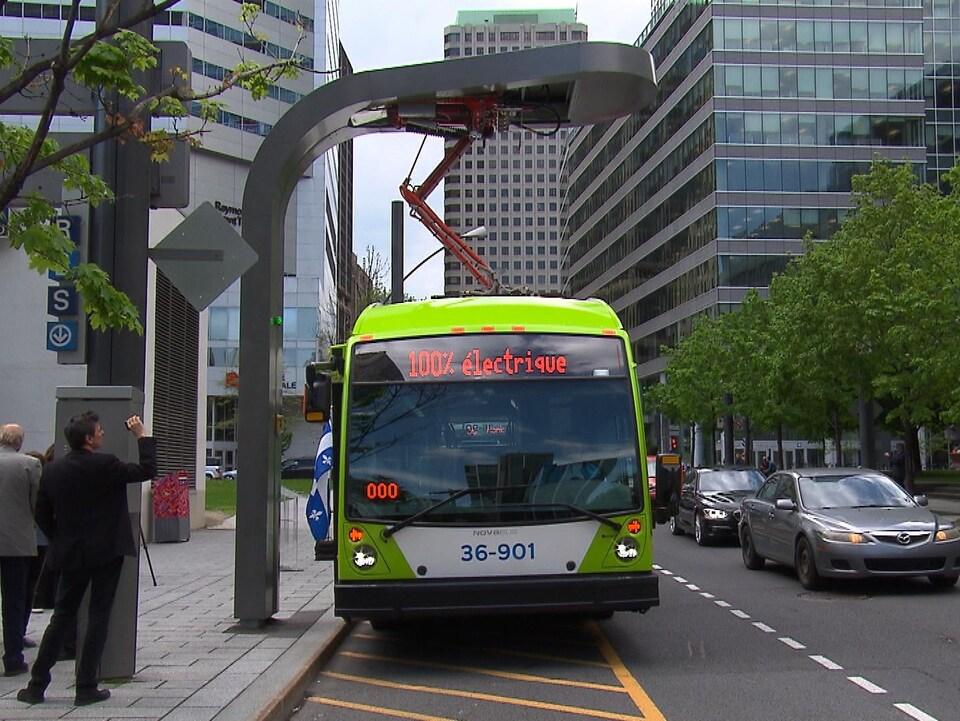 Un autobus qui affiche sur son écran frontal « 100 % électrique » est arrêté le long d'un trottoir.
