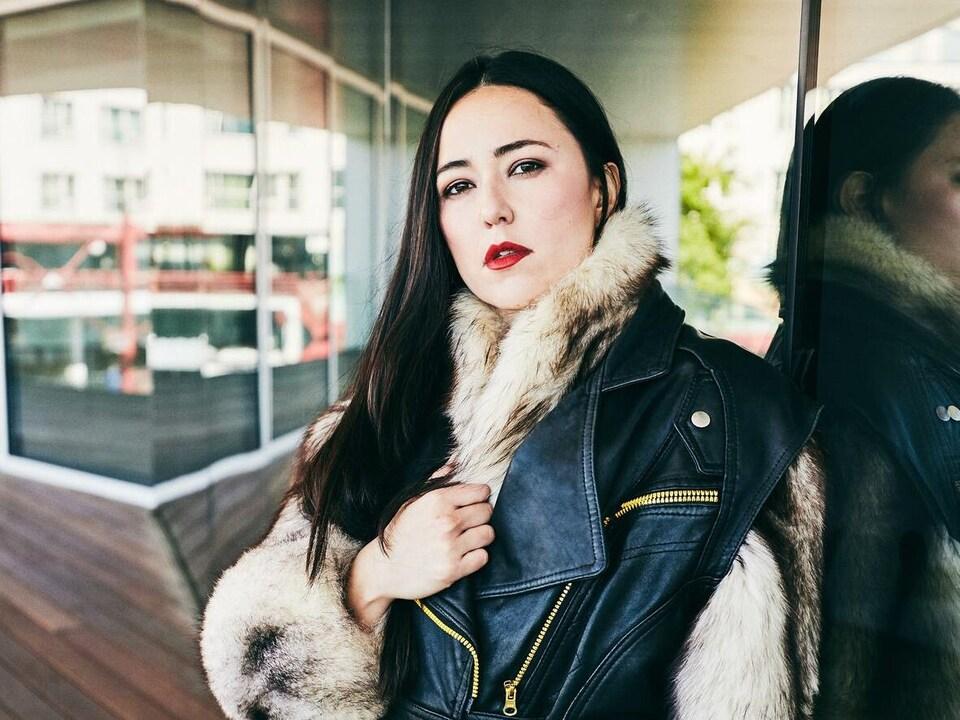 Une modèle porte un manteau fait de cuir et de fourrure.