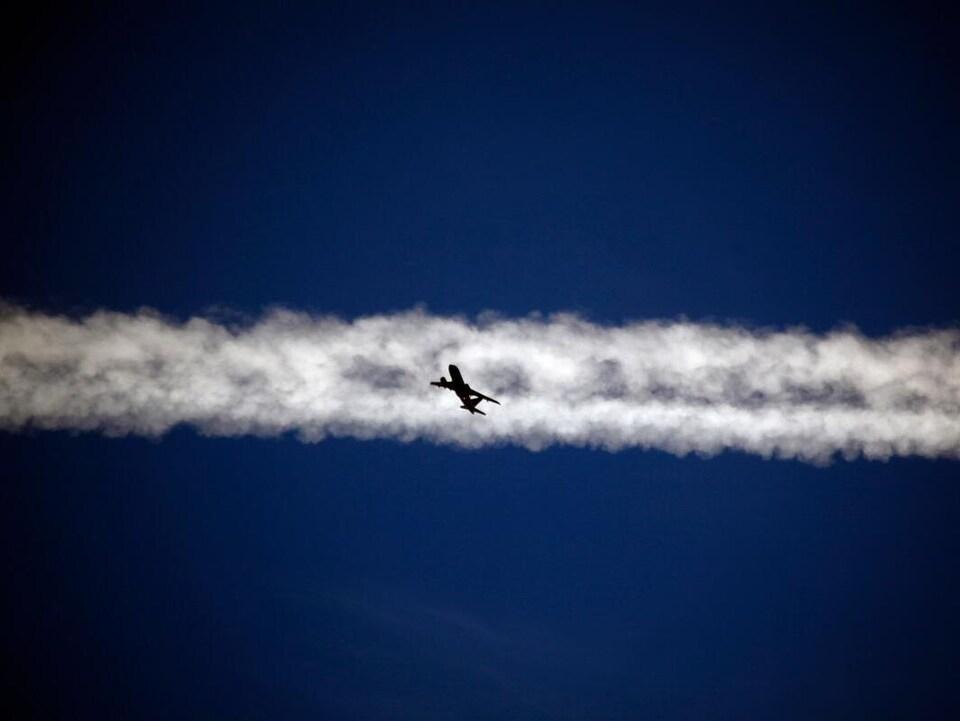 Un avion au centre d'une traînée blanche dans le ciel.