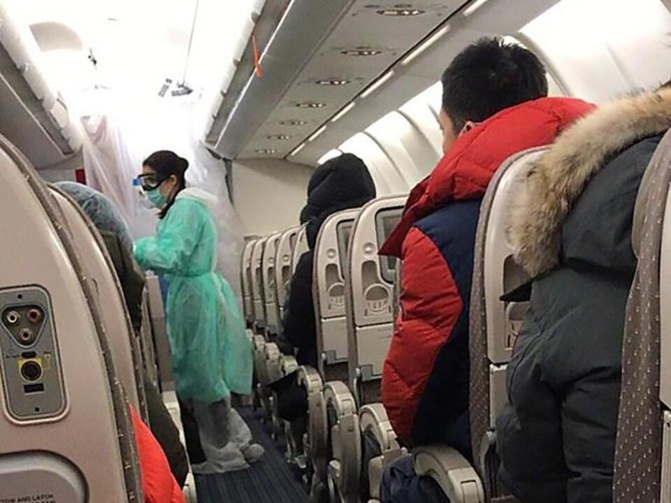 Des gens sont assis dans un avion. Une femme vêtue d'une tunique et d'un masque circule dans l'allée.