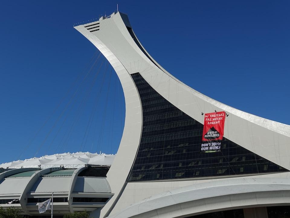Une banderole est vue de loin sur un édifice dont la tour est semble tenue par des câbles. La banderole dit «Ne salissez pas notre argent : stop pipelines».