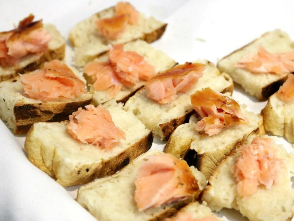 Des bouchées de saumon boucané sur de la bannique innue, lors d'un événement organisé à Montréal pour promouvoir le tourisme sur la Côte-Nord.
