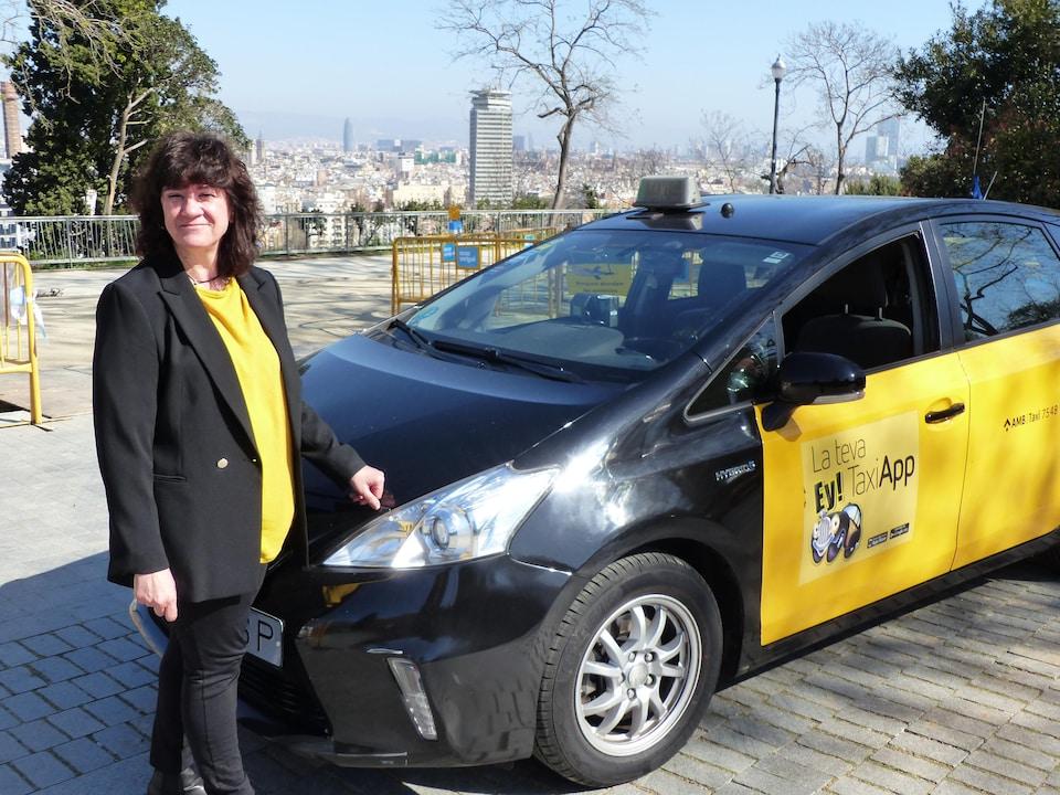 Marga Viudes devant son taxi.