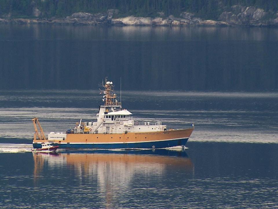 On voit le navire de recherche Coriolis II et le bateau pneumatique Colvert glisser côte à côte sur les eaux calmes de la rivière Saguenay.