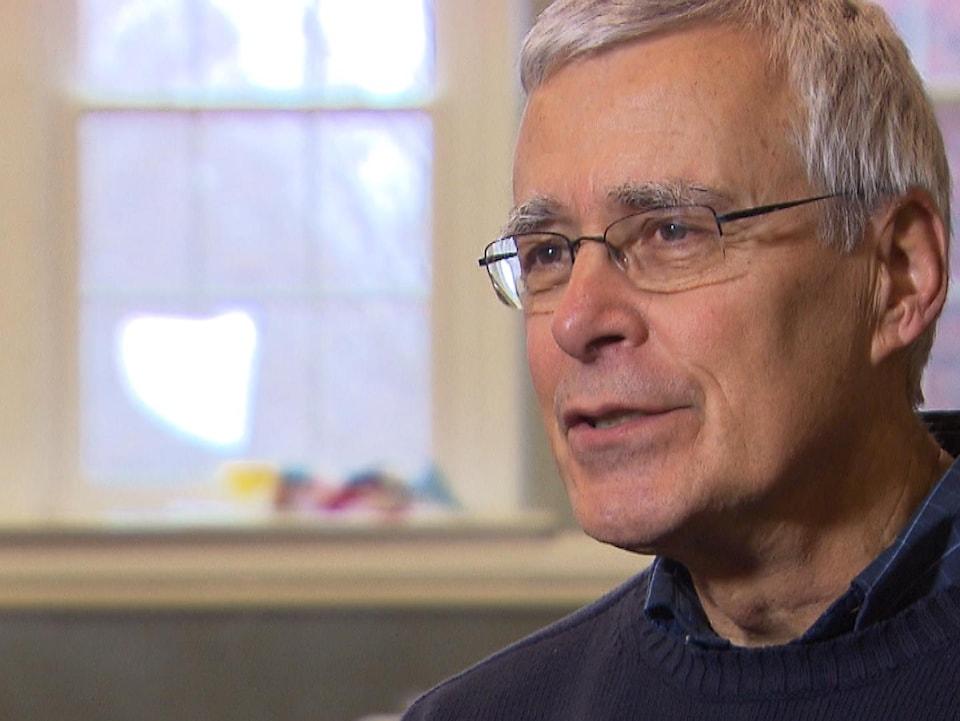 Un homme portant des lunettes discute avec un journaliste lors d'une entrevue.