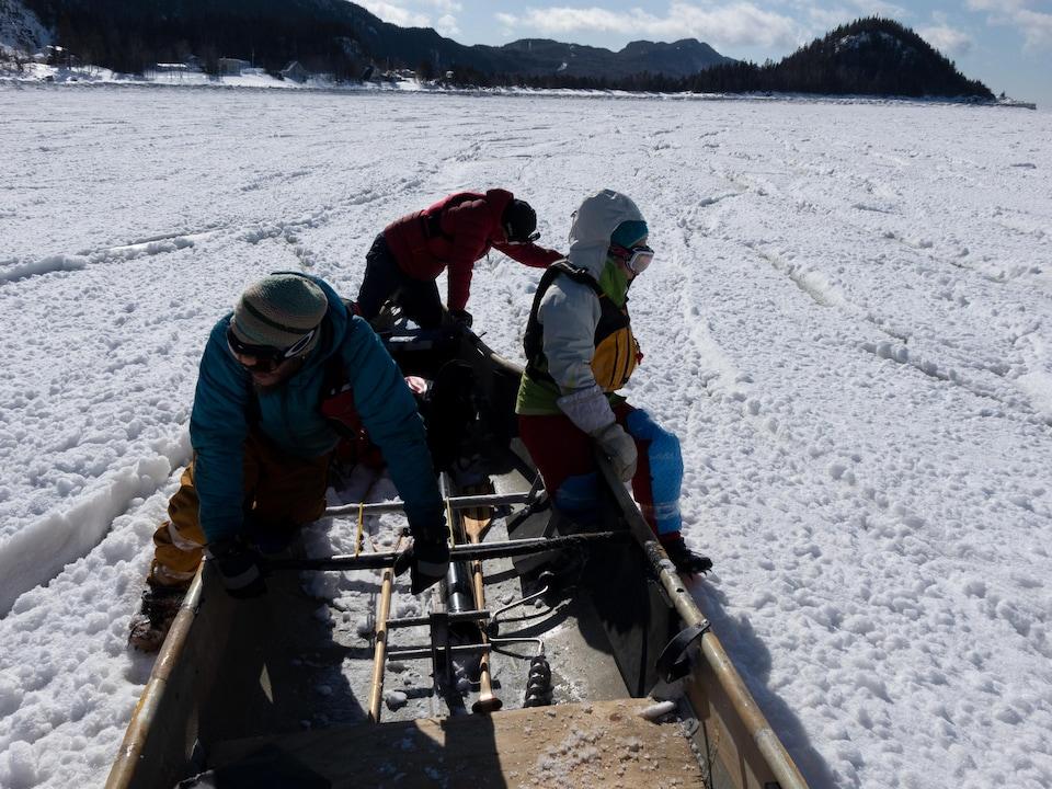 Trois personnes vêtues chaudement avec des manteaux d'hiver poussent un canot sur la glace.