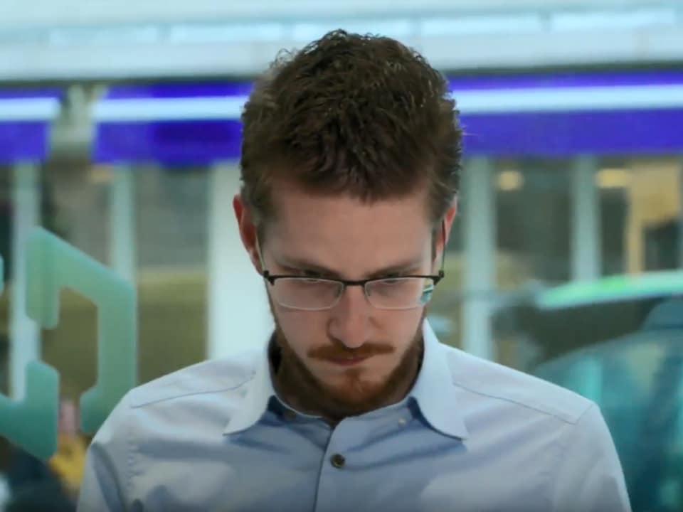 Un jeune homme portant une courte barbe et des lunettes regarde vers le sol.