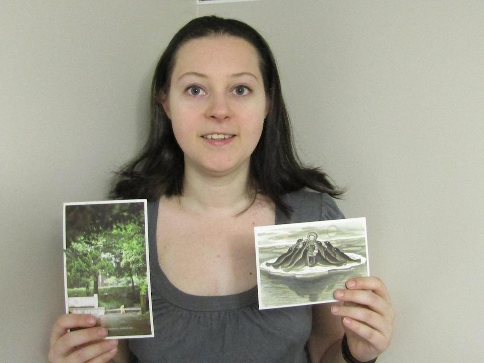 Une femme avec des cartes postales dans les mains.
