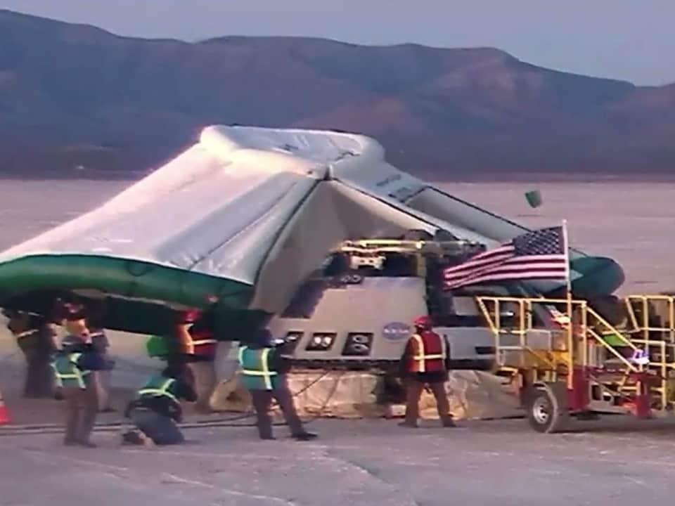 La capsule spatiale Starlilner est posée sur Terre sur des sacs gonflables, pendant que des techniciens posent une tente gonflable dessus.