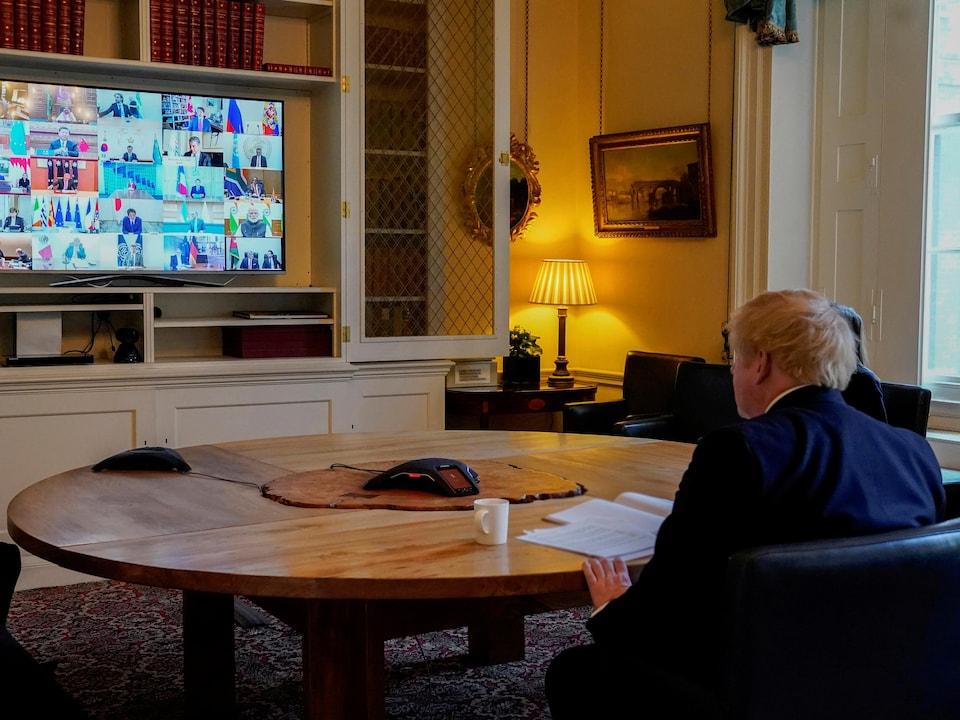 Boris Jonhson assis à une table ronde devant un écran affichant ses homologues du G20.