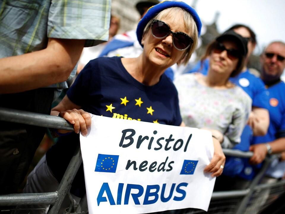 Une femme brandit une affiche sur laquelle est écrit : «Bristol a besoin d'Airbus».