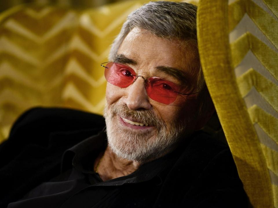 L'acteur Burt Reynolds est assis dans un fauteuil jaune et sourit à l'objectif.