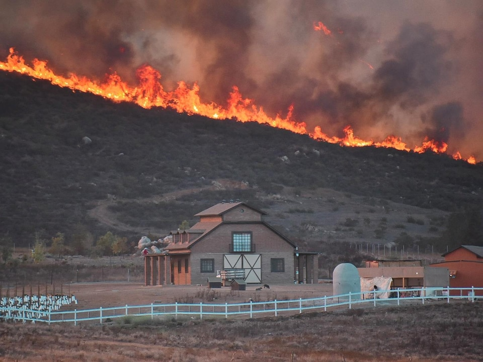 Une ferme menacée par un feu qui progresse.