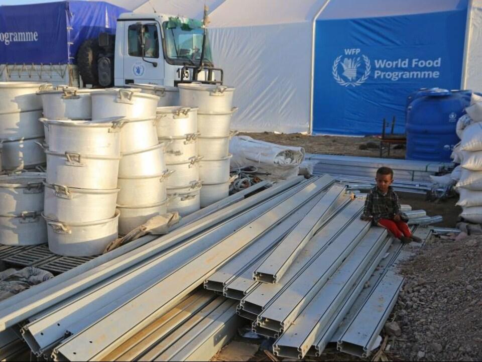 Un enfant est assis sur du matériel devant une tente à l'effigie du Programme alimentaire mondial de l'ONU.