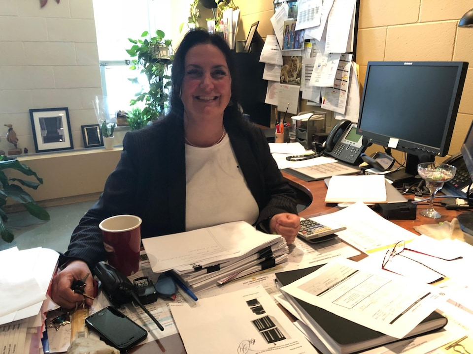 Caroline Boucher est assise à son bureau.