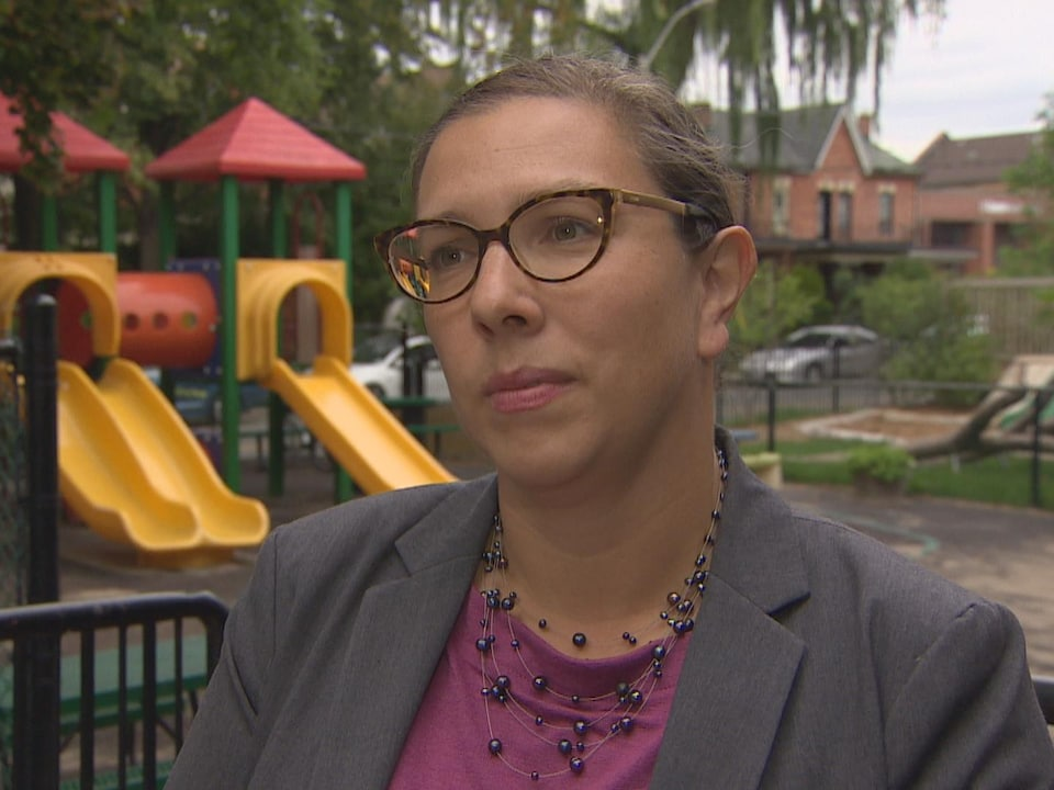 Une femme porte des lunettes devant un parc d'enfants.