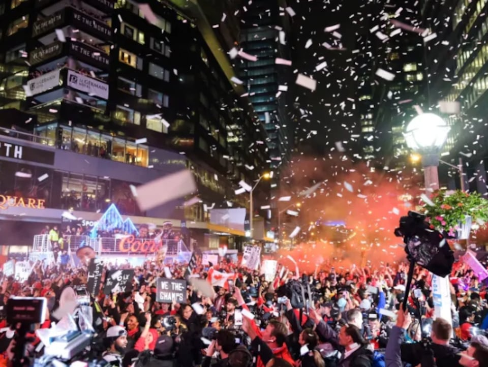 Des confettis tombent du ciel sur une foule en liesse.