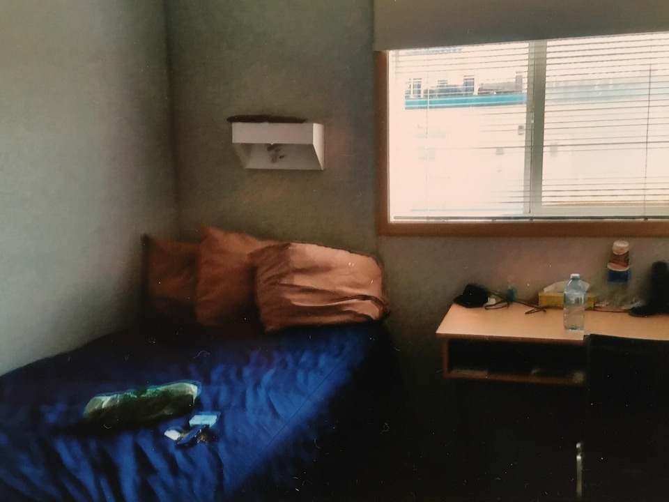 Un lit et un bureau près d'une fenêtre dans une petite chambre.