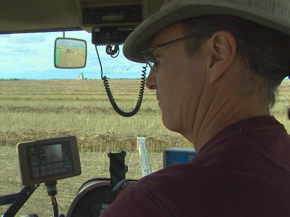 Un homme se trouve à bord d'une machinerie lourde qui est utilisée en agriculture. À l'extérieur du véhicule, on peut voir un grand champ.