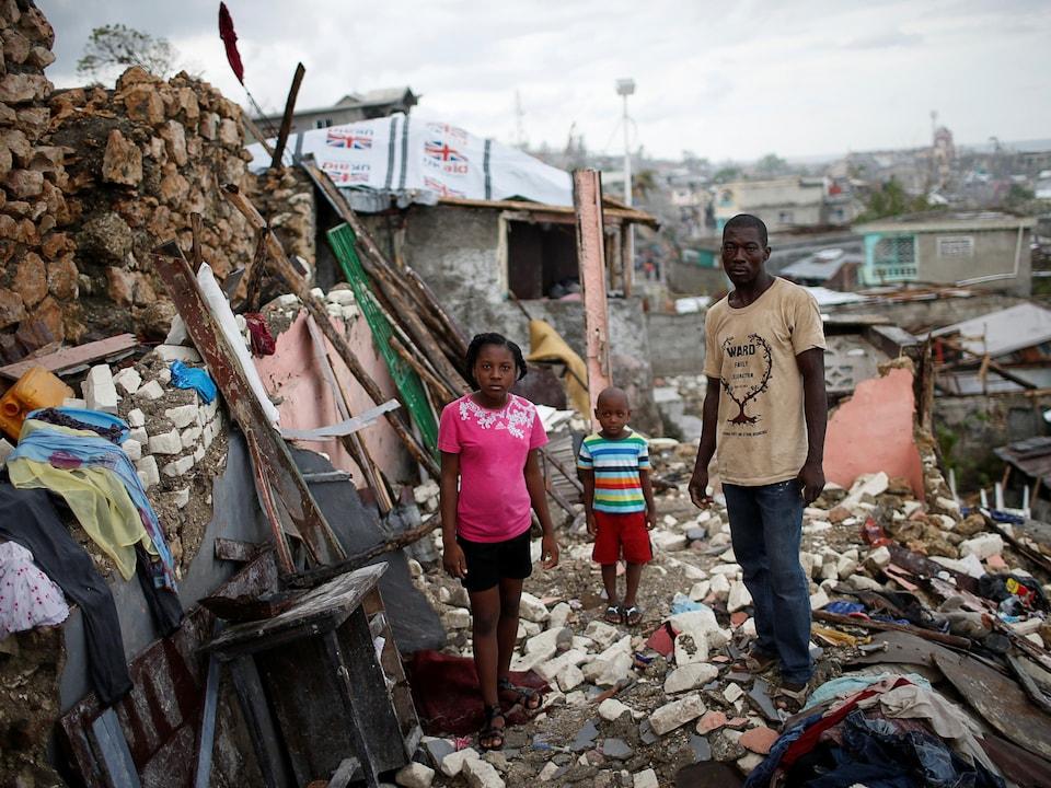 Une famille haïtienne désemparée prend la pose parmi les décombres de sa maison, après l'ouragan Matthew en 2016.