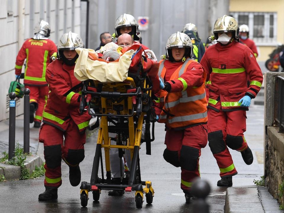 Quatre pompiers courent en poussant une civière sur laquelle se trouve une victime enroulée de couvertures et de bandages.