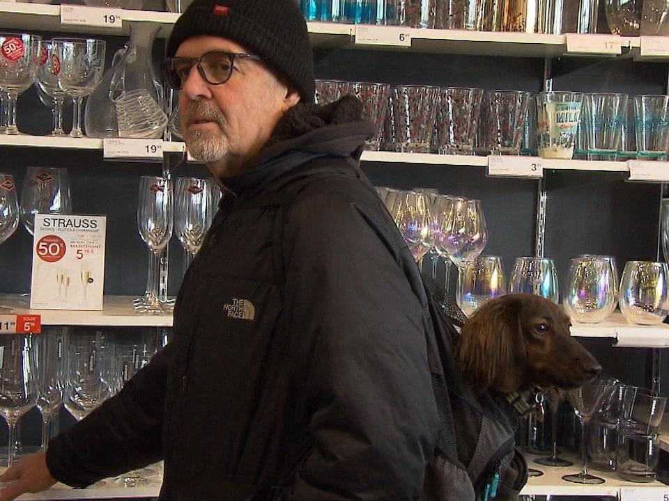 Un homme porte son chien dans un sac à dos.