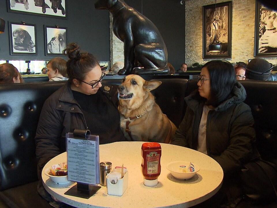 Deux filles et un chien autour d'une table dans le restaurant Hot Dog et cie