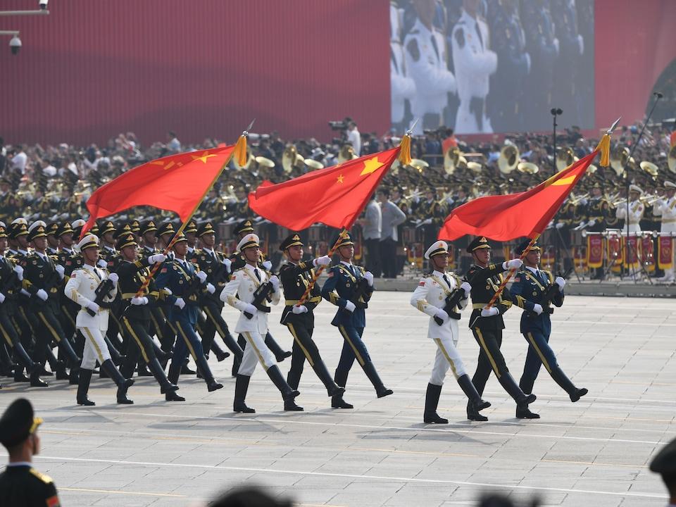 Des soldats chinois marchent en levant des drapeaux.