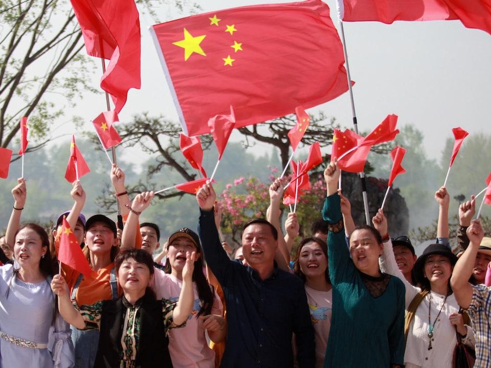 Des gens brandissent des drapeaux de la Chine en chantant une chanson patriotique.