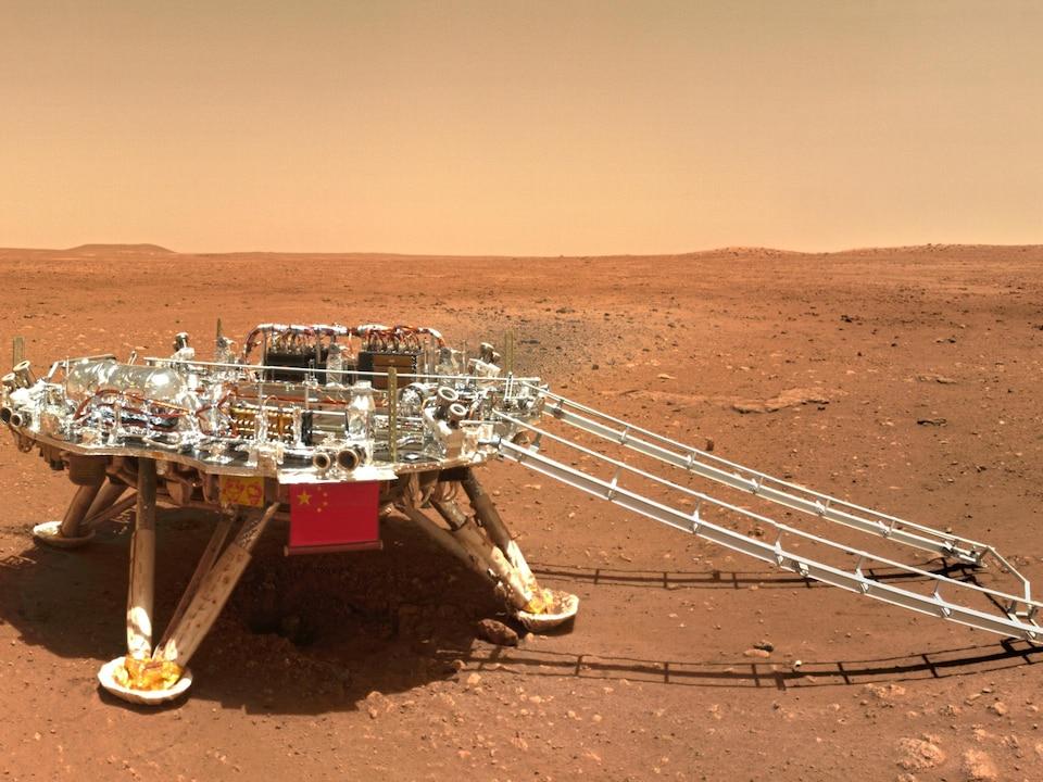 Un robot déploie un long bras dans un environnement désertique.