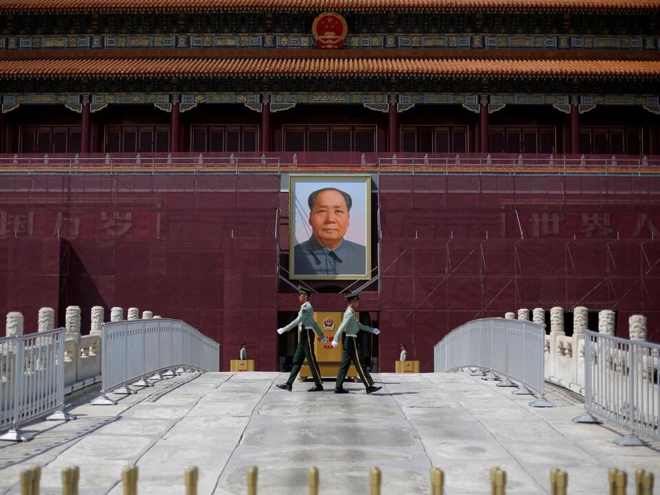 Deux agents montent la garde devant un portrait géant du dictateur communiste Mao.