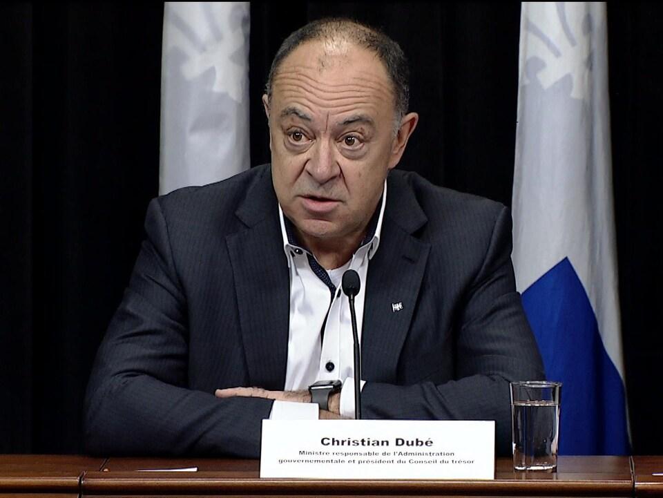 Christian Dubé, lors d'une conférence de presse, est assis derrière une table.