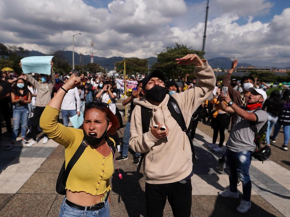 Des jeunes marchent dans une rue et scandent des slogans.