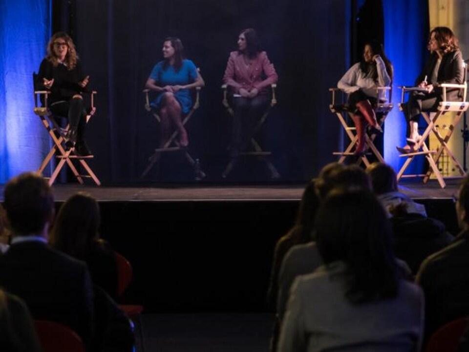 Les gens qui assistaient à la conférence pouvaient voir les quatre conférencières et l'animatrice devant eux.